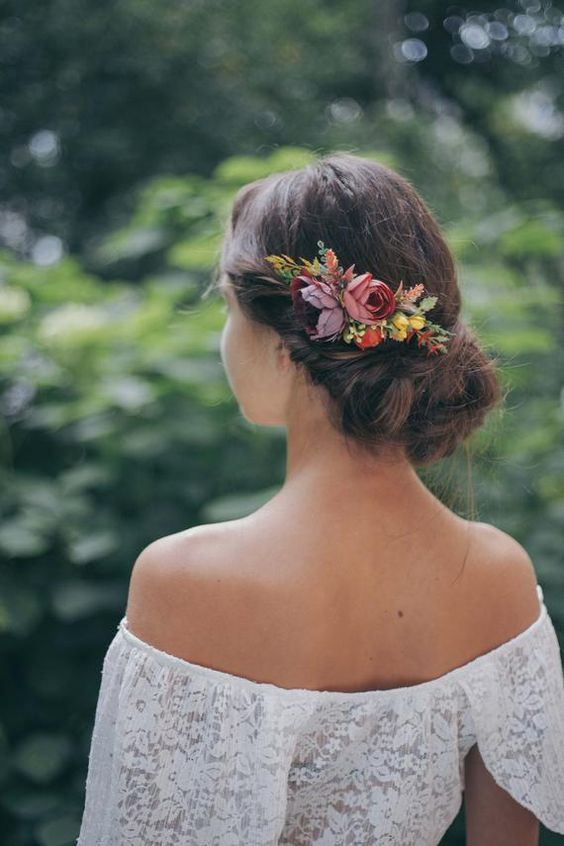 a twisted low updo with a bold floral accent with burgundy, purple and yellow blooms and greenery is a lovely idea for the fall