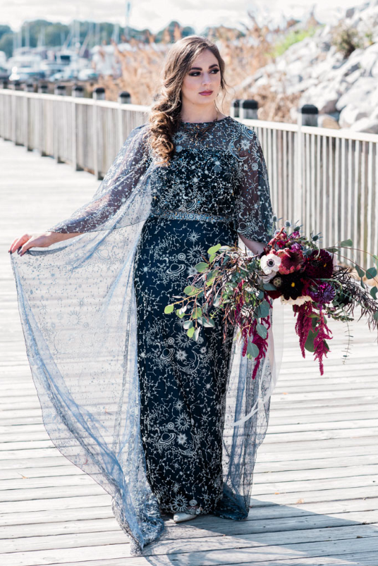 a unique midnight blue wedding dress with celestial prints and embroidery, an illusion neckline and a cape