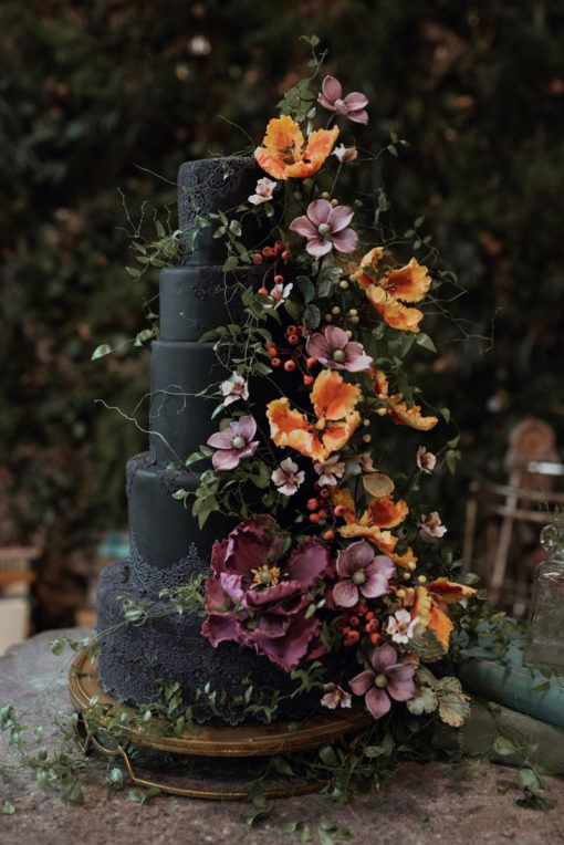 a very elegant and refined black wedding cake with purple, pink and orange sugar and usual blooms and greenery