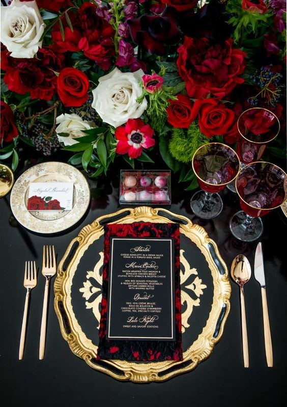 a very sophisticated and decadent wedding tablescape with gold chargers and cutlery, lush red roses and all black around