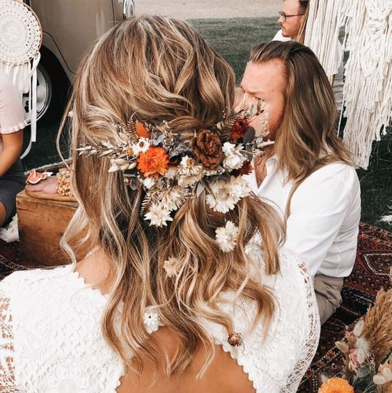 a wavy half updo with bright fresh and dried blooms and foliage is a lvoely idea for a fall boho bride