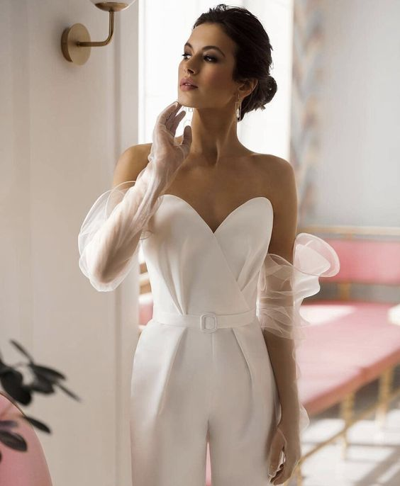 a white strapless jumpsuit paired with sheer long gloves with volume for a modern and refined bridal look