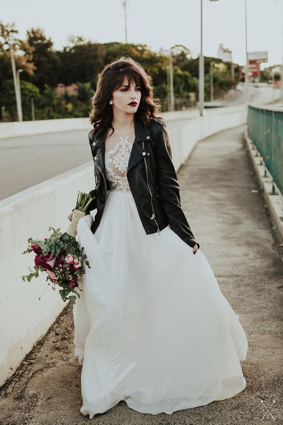 an edgy bridal look done with a black leather jacket and a dark lip plus a romantic wedding dress