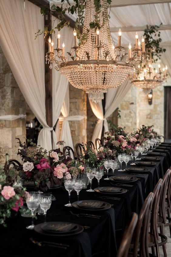 an elegant and opulent Halloween wedding table with a black tablecloth, plates, menus, blush and pink blooms and greenery