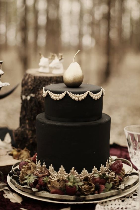 an elegant black haunted wedding cake with sugar patterns and a silver pear on top is a very stylish idea