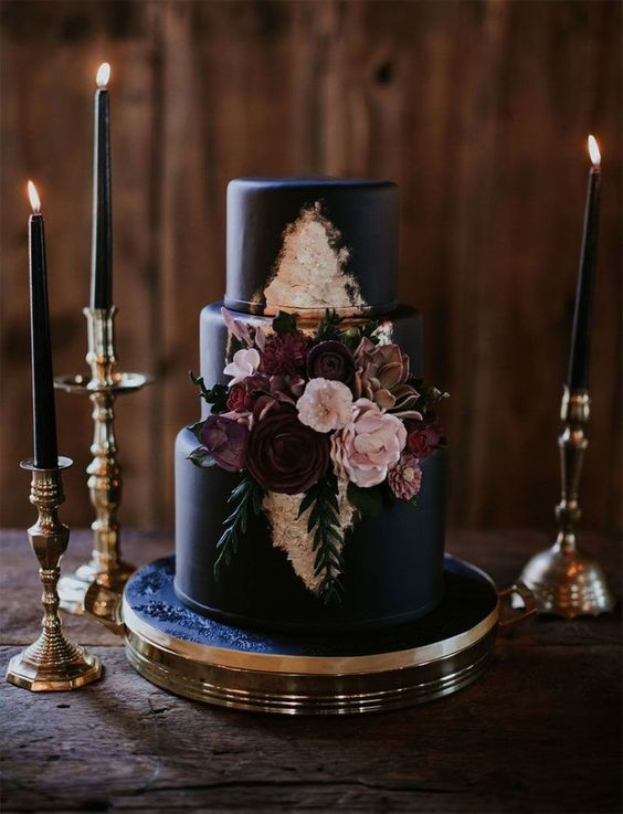 an elegant black wedding cake with gold leaf, burgundy and blush sugar blooms and greenery for Halloween