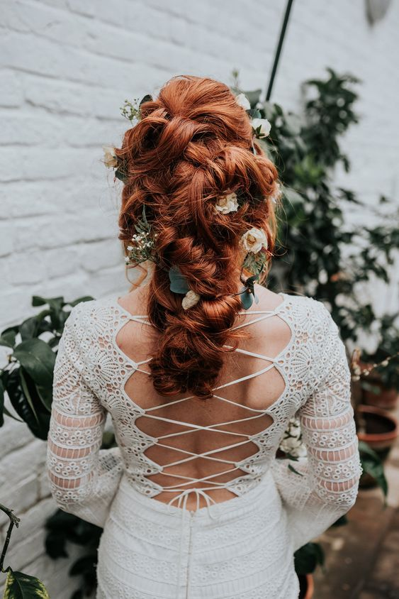 gorgeous ginger hair styled into a low updo with twists and texture, with neutral blooms and greenery is great for a fall wedding