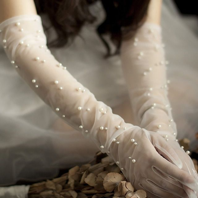 long sheer bridal gloves dotted with pearls look gorgeous and very delicate making a statement