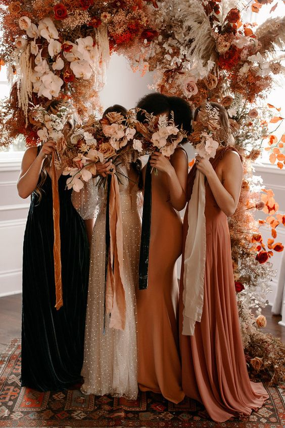 lovely mismatching rust, yellow and dark green bridesmaid dresses, with various silhouettes and necklines are amazing for a fall wedding
