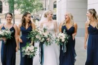 matching midnight blue draped maxi bridesmaid dresses with spaghetti straps and deep V necklines