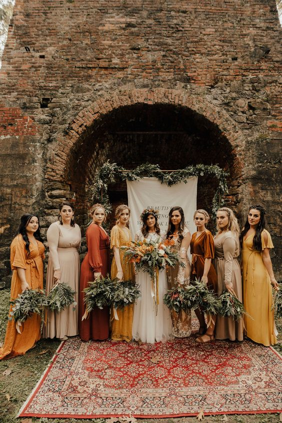 mismatching yellow, rust, nude and tan maxi bridesmaid dresses for a trendy and bold fall boho wedding