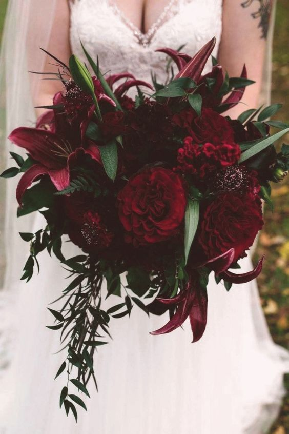 a Halloween wedding bouquet with pink, red and burgundy blooms, greenery and foliage is a colorful statement