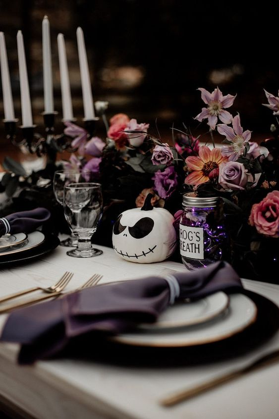 a beautiful Halloween wedding centerpiece of lilac and pink blooms, dark foliage, a skeleton pumpkin and some candles