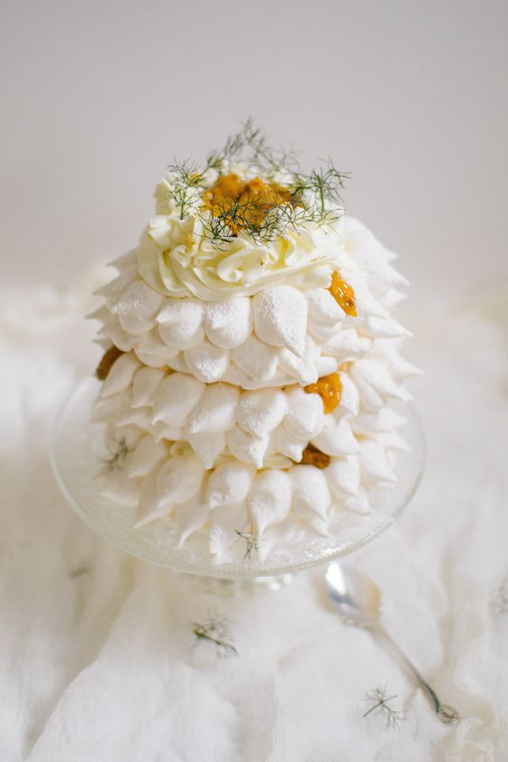 a beautiful meringue wedding cake with fresh fruits, whipped cream and greenery on top is amazing