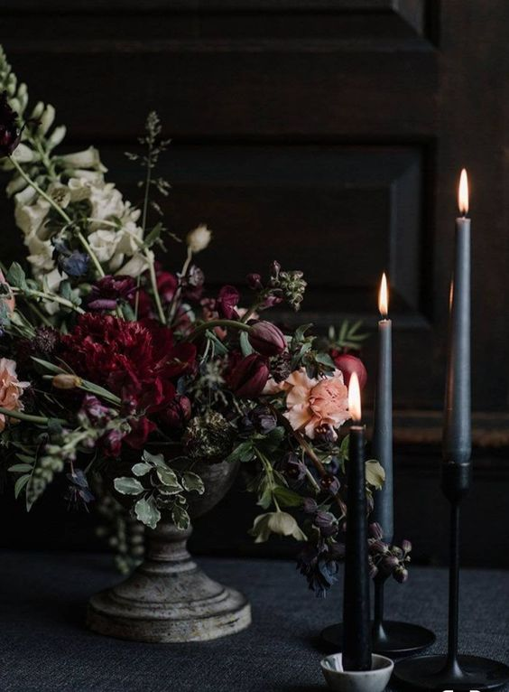 a beautiful, textural and sophisticated floral wedding centerpiece of burgundy and peachy blooms, greenery and thin and tall candles