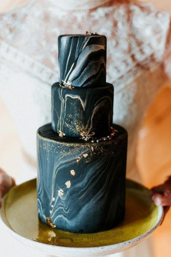 a black and grey marbleized wedding cake with gold glitter and foil