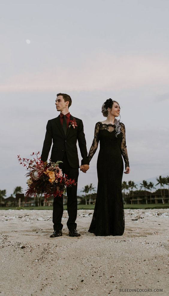 a black lace sheath wedding dress with an illusion neckline and long sleeves plus a fabric bloom headpiece for a Halloween wedding