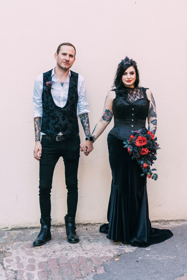 a black mermaid wedding dress with a lace sleeveless top and a velvet skirt plus a black corset over it for a sexy Addams look