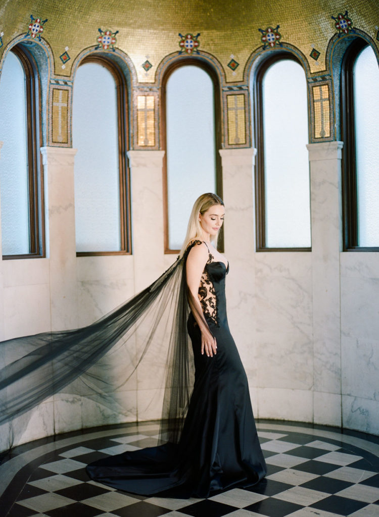 a black mermaid wedding dress with lace inserts on the sides and a long cape for a refined Halloween bride