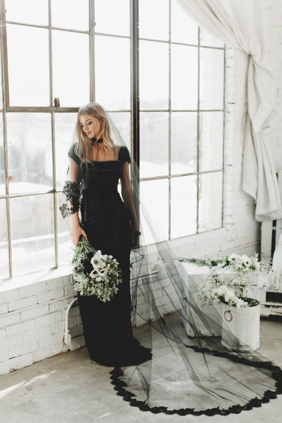 a black sheath wedding dress with cap sleeves, a black veil with a lace trim, a necklace
