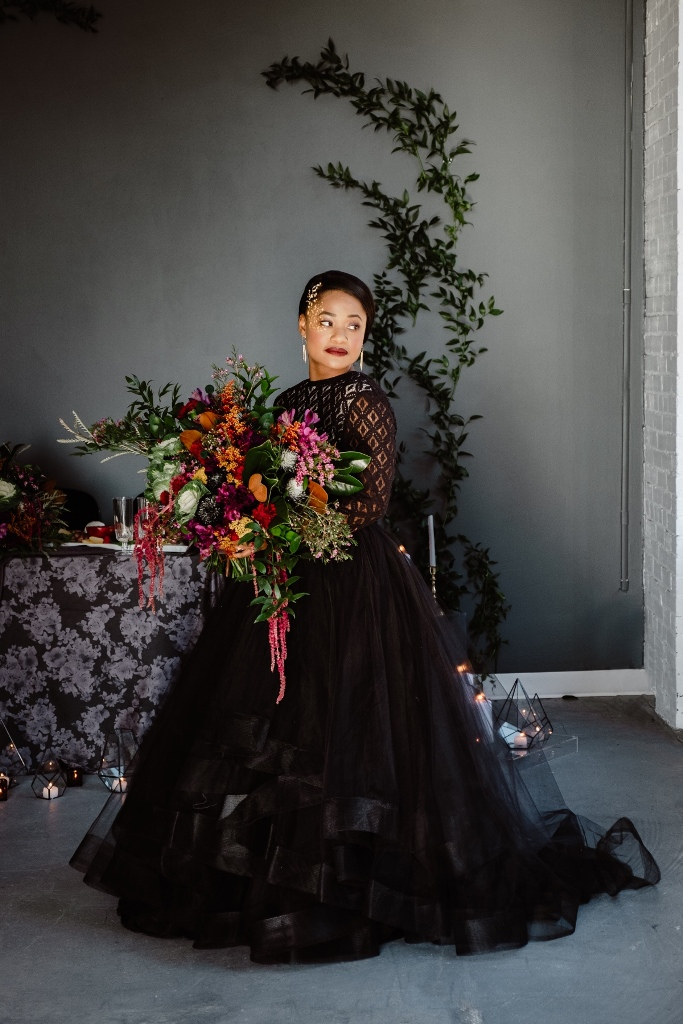 a black wedding ballgown with a crochet lace bodice and long sleeves plus a tiered ruffle skirt and an open back