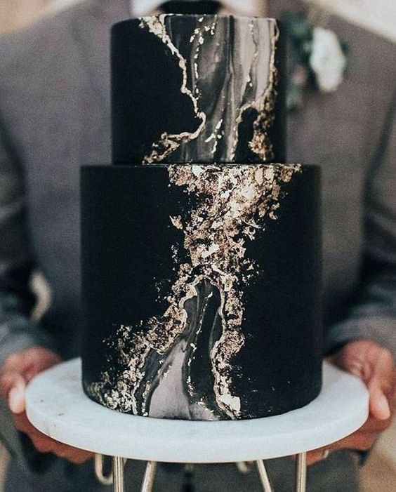 a black wedding cake wiht a marble effect and touches of gold foil