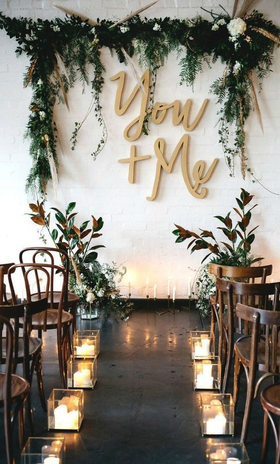 a boho indoor wedding backdrop with a greenery, grass and bloom wedding arch, letters and branch arrangements and candles on the floor