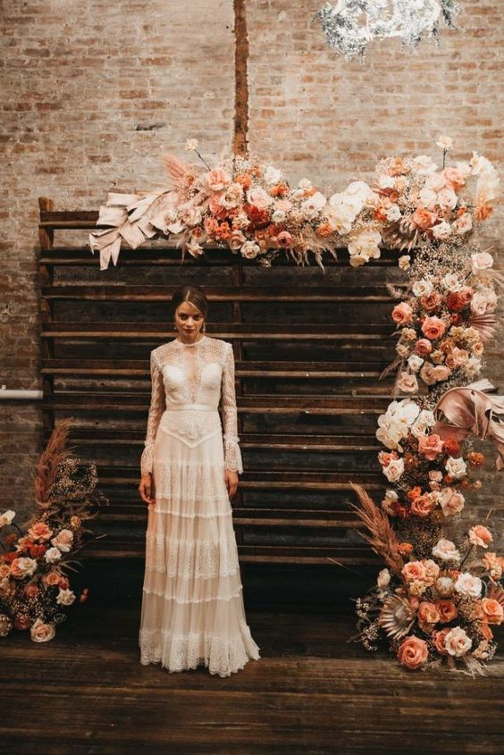 a boho rustic wedding backdrop mad eof stained reclaimed wood,pink, rust, white blooms, painted grasses and large foliage