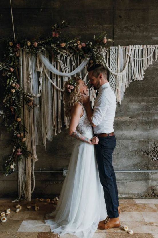 a boho wedding backdrop with macrame and ribbons, greenery and blooms attached to the wall
