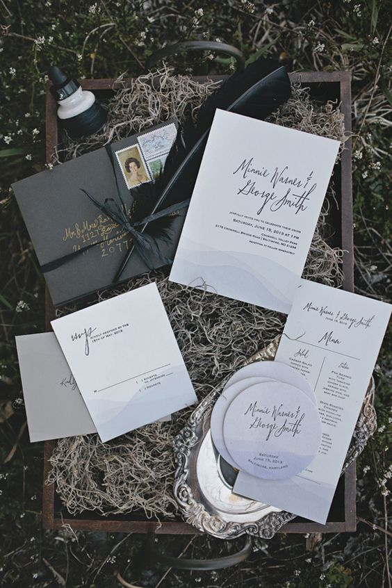 a box wit hay, modern wedding invitation suite, a black envelope, a large feather, elegant calligraphy