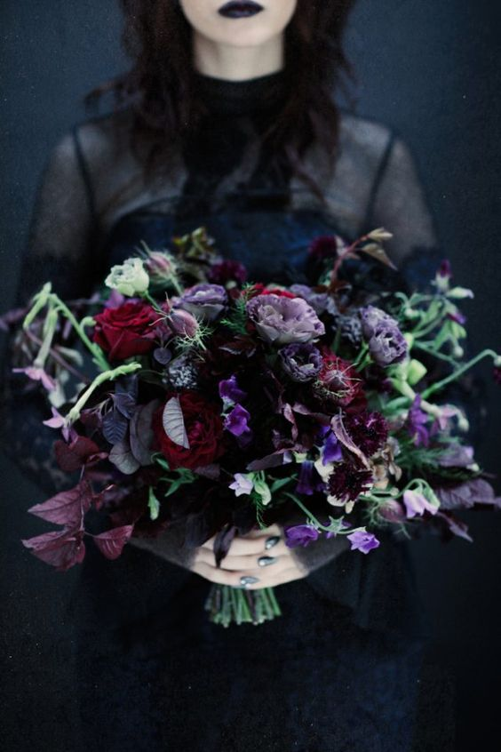 a catchy Halloween wedding bouquet in purple, burgundy, blue, with dark foliage, greenery and much texture