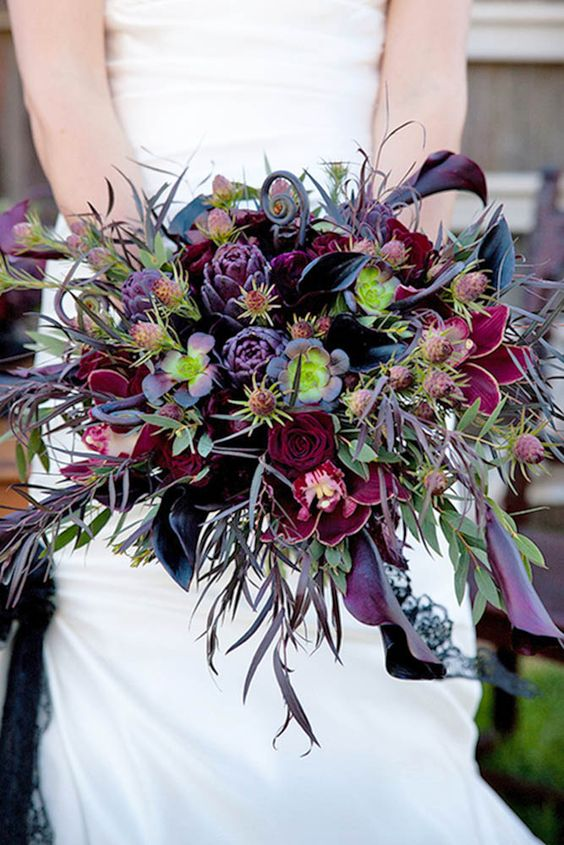 a catchy Halloween wedding bouquet with purple and burgundy blooms, greenery, thistles and foliage is wow