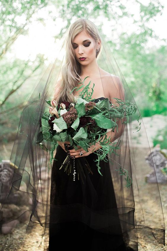 a catchy dark bloom wedding bouquet with large leaves and more greenery, with an embellished wrap