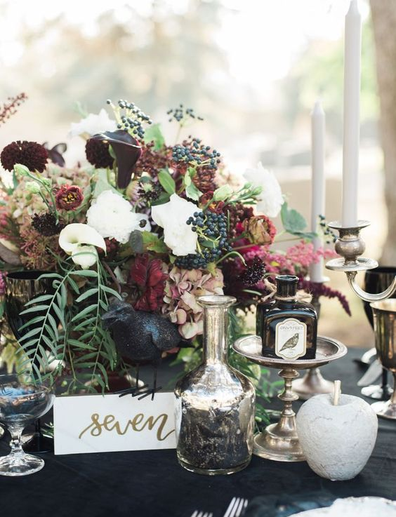 a chic Halloween wedding centerpiece of white and deep burgundy blooms, greenery, berries and leaves plus a candelabra