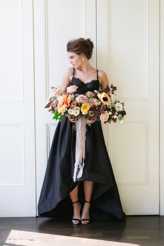 a chic black spaghetti strap wedding dress with a lace bodice and a high low skirt looks very modern and romantic