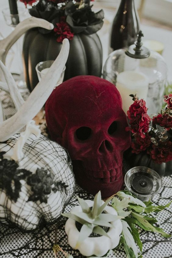 a cluster wedding centerpiece of a burgundy plush skull, a pumpkin planter with a succulent, a white pumpkin in black lace and antlers