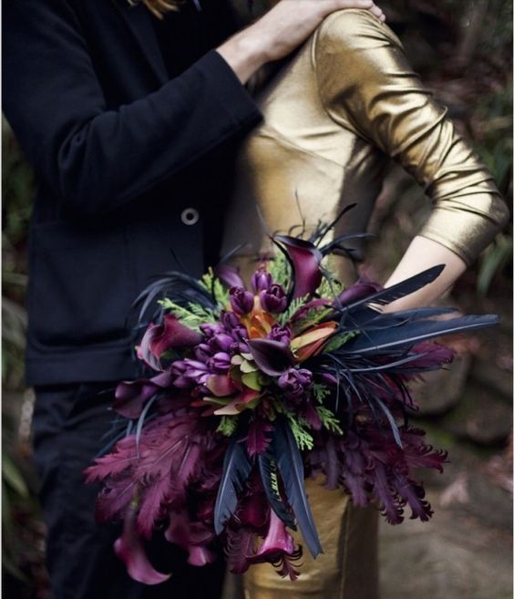 a colorful Halloween bouquet with purple blooms, purple and black feathers and some greenery