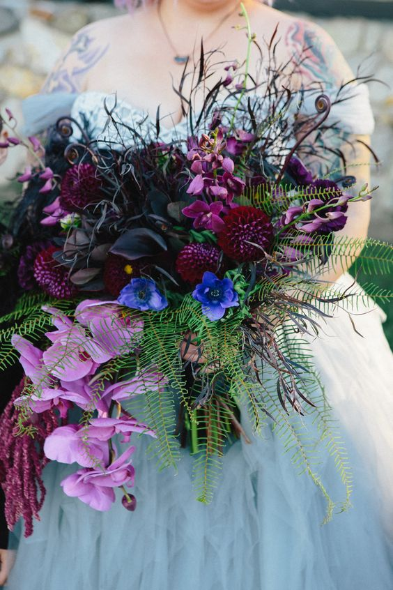 a colorful Halloween wedding bouquet with deep purple, purple, blue and black blooms, fern, twigs and foliage is wow