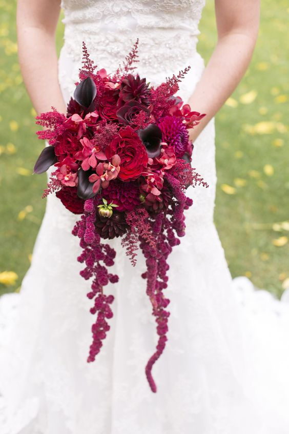a colorful Halloween wedding bouquet with red, pink and hot pink blooms, deep purple blooms and cascading lisianthus