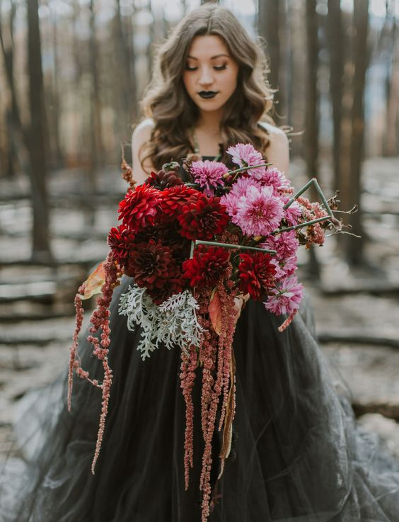 a colorful and textural wedding bouquet of pink, red and rust cascading blooms, pale millet and stems to stand out with a black wedding dress
