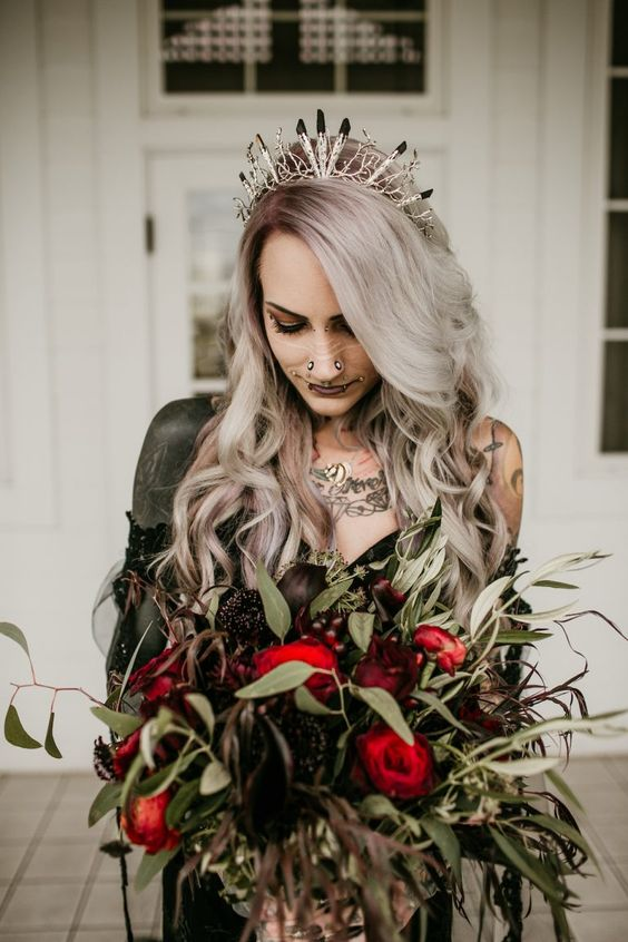 a dark Halloween wedding bouquet with black and red blooms and much greenery is stylish and bold
