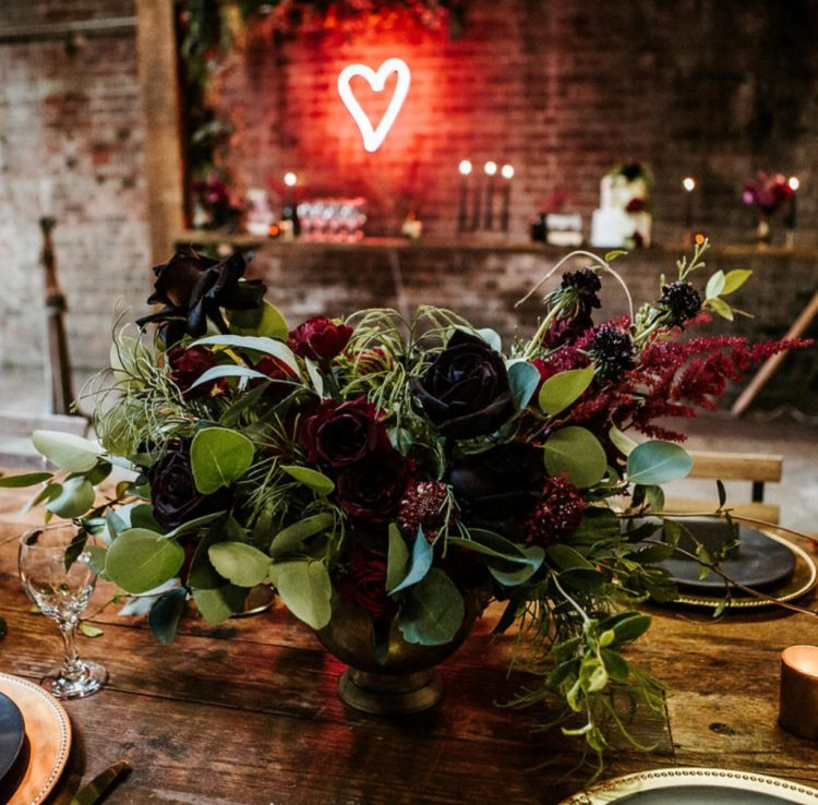 a dark burgundy and black rose wedding centerpiece with greenery and eucalyptus is classics for Halloween