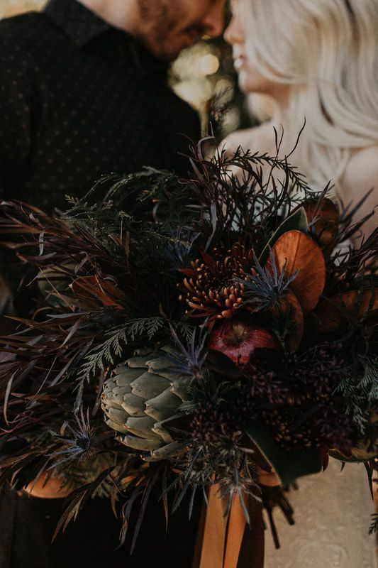 a dark textural wedding bouquet of pink and burgundy blooms, an artichoke, dark foliage and textural greenery plus thistles