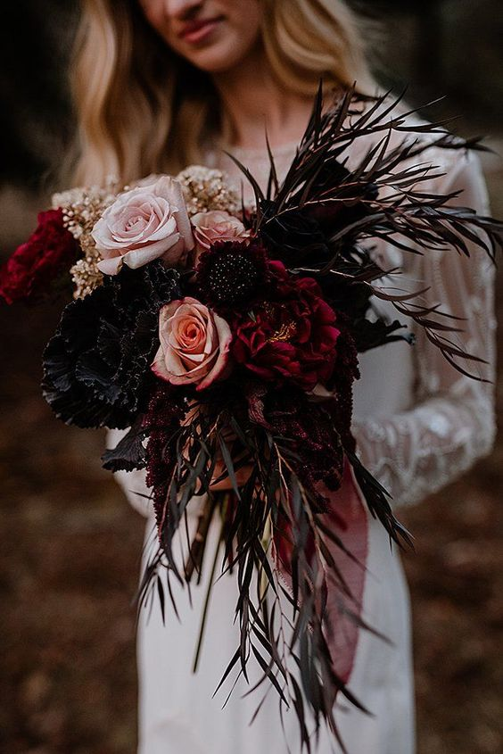 a dark wedding bouquet of dark, burgundy and blush blooms, dark foliage and some glittered touches