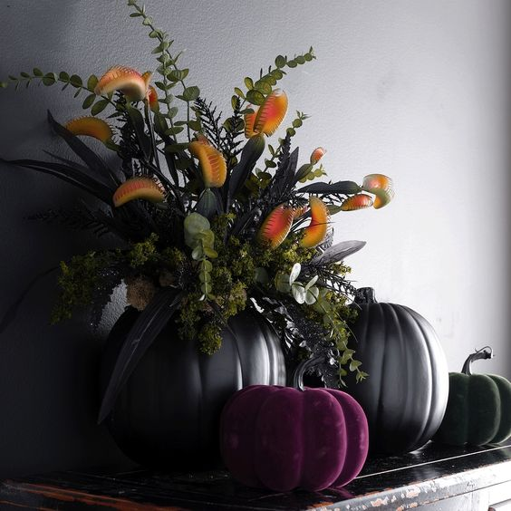 a fantastic Halloween wedding centerpiece of black and purple pumpkins, black leaves and bold blooms is a gorgeous idea