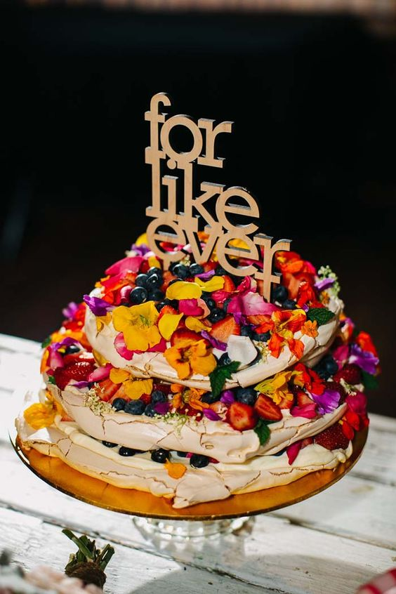 a fantastic pavlova wedding cake with bold edible flowers, petals, fresh berries and fruits and a lovely gold topper