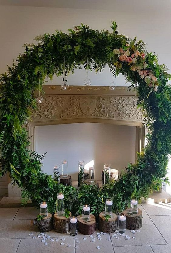 a faux fireplace, a greenery round altar with blooms and candles on stumps and hanging down from the wreath