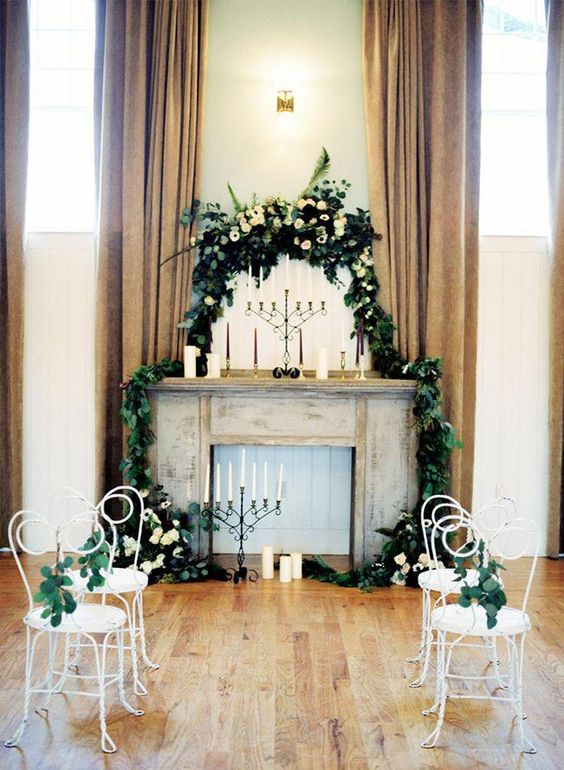 a faux fireplace with candles, greenery and white blooms plus candles on the floor and mantel