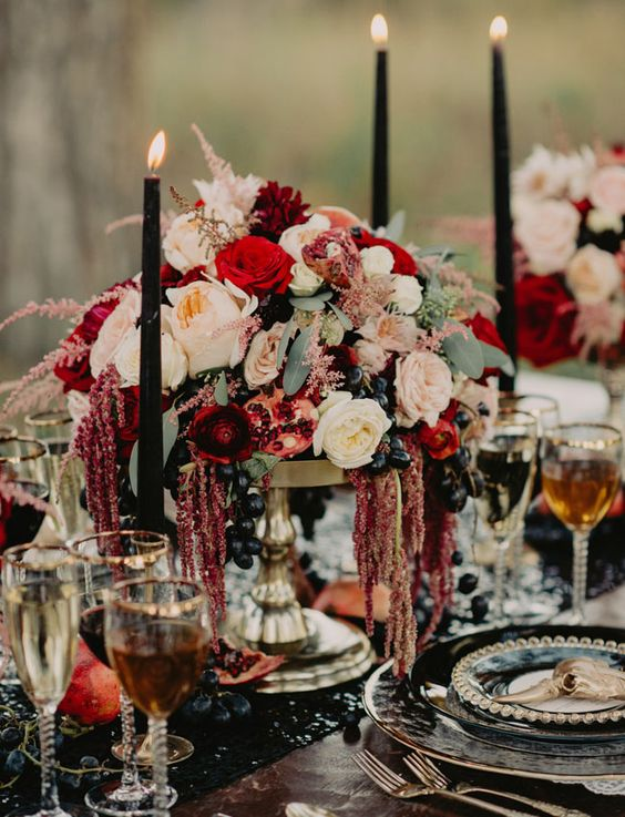 a gorgeous decadent Halloween wedding centerpiece of a tall gold bowl with blush and deep red blooms, greenery, grapes and with black candles around