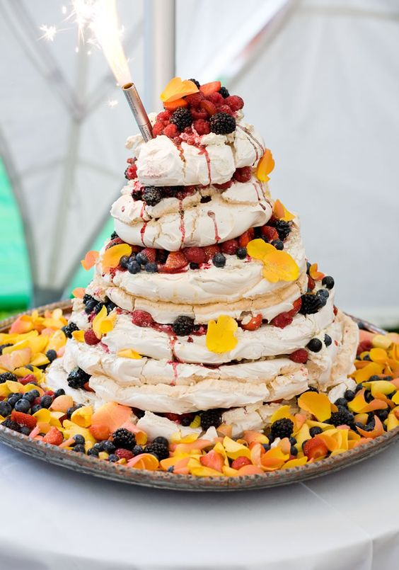 a gorgeous pavlova wedding cake with lots of fresh fruit, berris and bright petals is a very bold and delicious idea